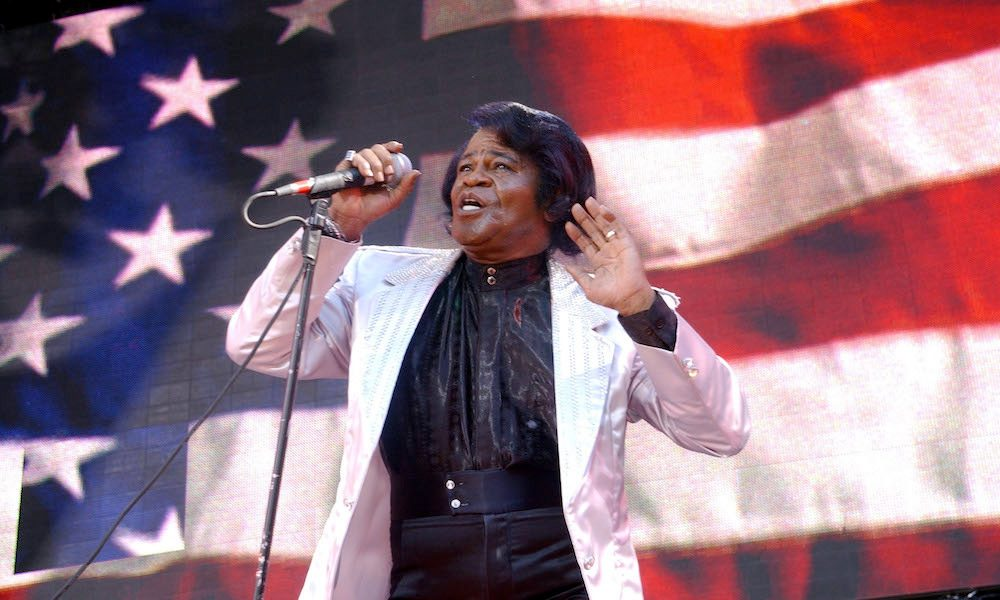 James Brown, singer of the patriotic song and 4th of July anthem Living in America, singing in front of an American flag